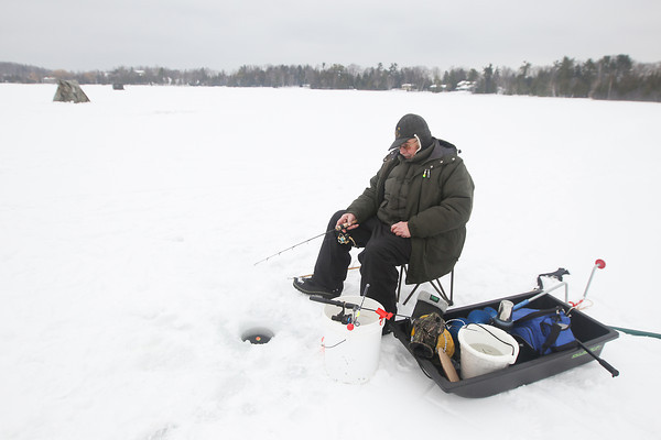 "Record-Eagle/Keith King<br /> Frank Strehl, of Leland Township, ice fishes for smelt Friday on Cedar Lake in Elmwood Township during milder temperatures compared to those earlier in the week. ""First part of the week I wasn't going anywhere but by the wood stove,"" Strehl said."