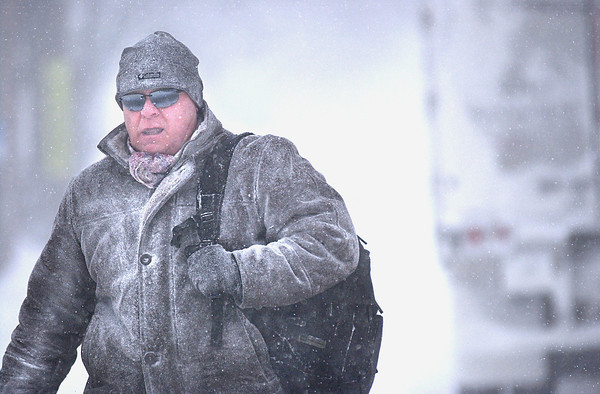 Record-Eagle/Nathan Payne<br /> Greg Parry walks to work downtown Traverse City early Monday morning while strong winds and snow whipped up white-out conditions across the region.