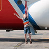 """Record-Eagle/Jan-Michael Stump<br /> Connor Reed, 6, of Traverse City, leaps in attempt to touch one of the propellers on the U.S. Coast Guard's HC-130 """"Hercules"""" aircraft during Friday morning's """"open ramp"""" at U.S.C.G. Air Station Traverse City. The plane was one of  several on display that will be part of this weekend's National Cherry Festival Air Show over West Grand Traverse Bay."""