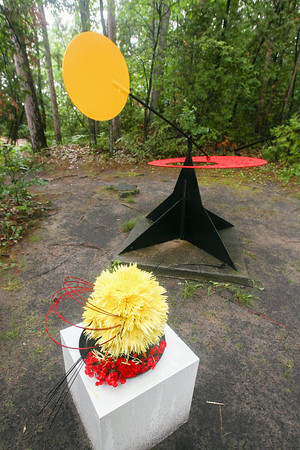 """Record-Eagle/Keith King<br /> A floral interpretation designed by Derek Woodruff and arranged by Sharon Lanier stands near the sculpture, """"Sun Over the Red Sea,"""" by Dave Vande Vusse, at the Elk Rapids Day Park Walk of Art Sculpture Exhibit during the Elk Rapids Garden Club Presenting Artful Gardens garden walk."""