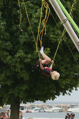 Record-Eagle/Keith King<br /> Quinlan Bollwitt, 8, of Davison, does a backflip on a bungee trampoline during the National Cherry Festival.