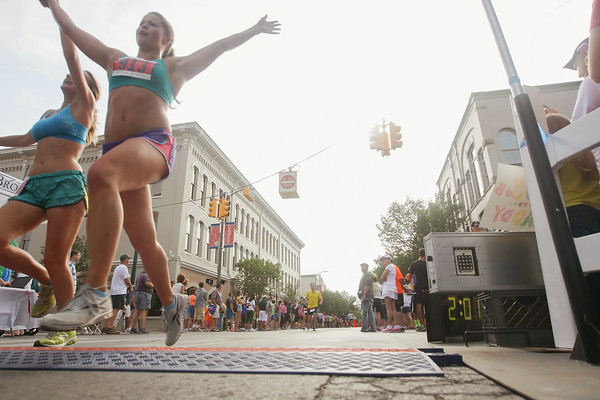 Record-Eagle/Keith King<br /> Eryn Scannell, of Grand Blanc, raises her hands after crossing the finish line during the National Cherry Festival Festival of Races.