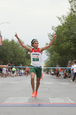 Record-Eagle/Keith King<br /> Clark Ruiz, of Big Rapids, finishes first in the men's 5K during the National Cherry Festival Festival of Races.