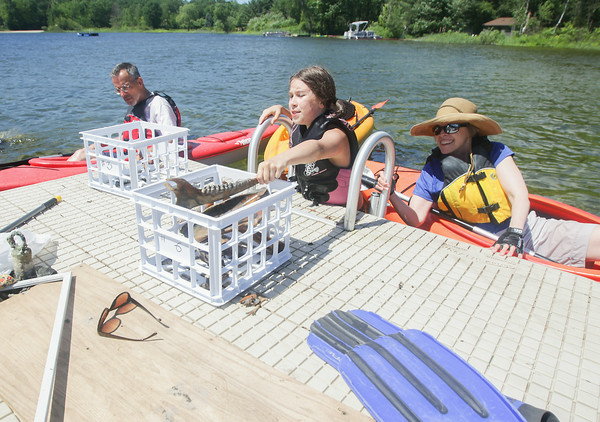 Record-Eagle/Keith King<br /> Sonja Daniels Moehle, 10, of Benzie County, places a jaw bone in a crate as her grandfather John Daniels, left, of Traverse City, and grandmother, Kathy Daniels, right, of Traverse City, sit near in kayaks during an excavation of elk bones in Benzie County.
