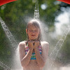 Record-Eagle/Jan-Michael Stump<br /> Mckenna Dorvinen, 11, of Kingsley finds relief from Wednesday's heat on the splash pad in Brownson Memorial Park.