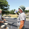 Record-Eagle/Keith King<br /> Brion Arbenowske, right, drinks cold water that Dockside Party Store gave to him and his coworker, Gary Blakeney, both with Story Roofing Company, on Wednesday. The two were working on the roof of Dockside Party Store in Traverse City.