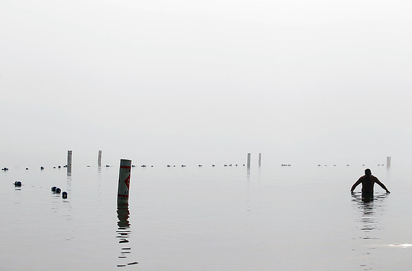 Record-Eagle/Jan-Michael Stump<br /> Richard Porter, of Kalkaska County, wades in the water at Clinch Beach on Tuesday morning.