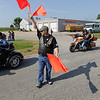 Record-Eagle/Keith King<br /> Steve DeBusschere, Northern Chapter Harley Owners Group member, directs motorcyclists as they park Sunday near Classic Motor Sports prior to the start of the annual Ride for Father Fred.