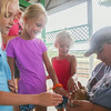 Record-Eagle/Keith King<br /> Gracynn Smith, from left, 7, Marin Smith, 8, and Brynn Smith, 4, all of Colorado, pet a baby rabbit belonging to Kassie Pierson, of Fife Lake, and a member of the Farm Friends 4-H Club, during the Kalkaska County Agricultural Fair at the Kalkaska County Fairgrounds.