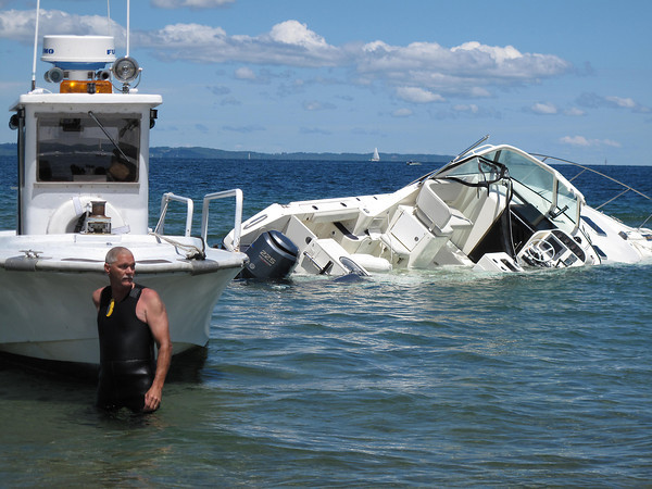 Record-Eagle/Glenn Puit<br /> Terry Kiersey, of Traverse Dockside Marine, waits for the owner of a sunken boat to arrive at the shoreline of Grand Traverse Bay on Wednesday afternoon. The boat sank in heavy waves Tuesday — Kiersey said it appears both anchors on the boat were deployed, which played a role in its sinking. Kiersey identified the boat as a 34- or 38-foot Pursuit.