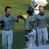 Record-Eagle/Jan-Michael Stump<br /> Beach Bums center fielder Kyle Culligan (23) congratulates Brian Heere (left) and Ryan Still (right) after Heere and Still scored on Jeff Flagg's two-run single in the first inning against the Joliet Slammers Monday at Wuerfel Park.