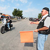Record-Eagle/Keith King<br /> Larry Shugart, of Suttons Bay, and a Northern Chapter Harley Owners Group member, directs motorcyclists as they arrive Sunday, July 22, 2012 for the 20th annual Ride for Father Fred to benefit the Father Fred Foundation. The event is sponsored by the Northern Chapter Harley Owners Group (HOG).