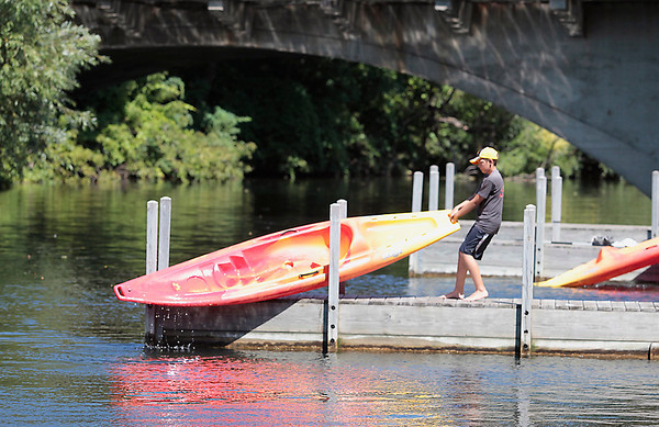 Record-Eagle/Jan-Michael Stump<br /> Trevor Damron, 13, of Amherst, OH, pulls his kayak from the Boardman River near the Cass Street bridge for a portage around the Union Street dam while paddling with his family on Tuesday afternoon.