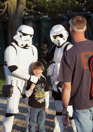 """Record-Eagle/Keith King<br /> Evan Chase, 5, of Traverse City, has his photo taken by his father, Chris, as he stands with characters from """"Star Wars"""" movies at the Open Space."""