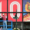 Record-Eagle/Nathan Payne<br /> Workers stick some of the last panels of a large Traverse City Film Festival sign to windows on a building at the corner of Cass and Front streets.