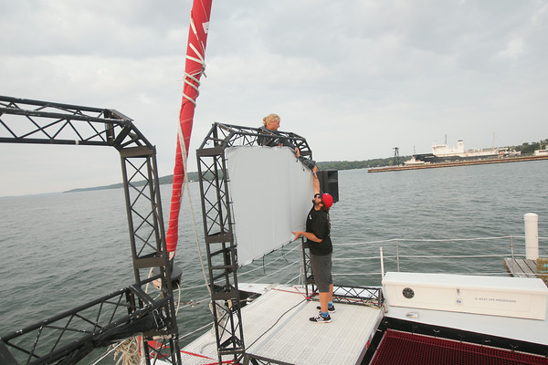 Record-Eagle/Keith King<br /> Chien Nowland, left, captain/owner of the Nauti-Cat, and Steffan Phillippo, first mate on the Nauti-Cat, put a screen up on the Nauti-Cat in preparation for a movie to be played on the catamaran during the Traverse City Film Festival.