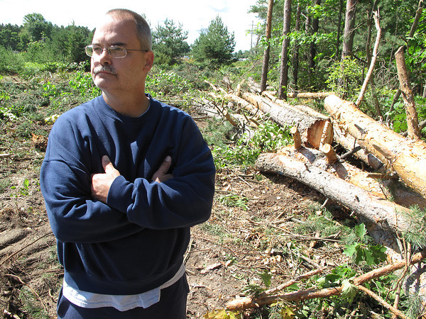 Record-Eagle/Matt Troutman<br /> TRAVERSE CITY — Jon Grist on Thursday stands in what remains of a pine grove on his Blair Township property. Crews contracted by Michigan Electric Transmission Company cut down his trees this week to create a wider right-of-way for their 138,000-volt power transmission line.