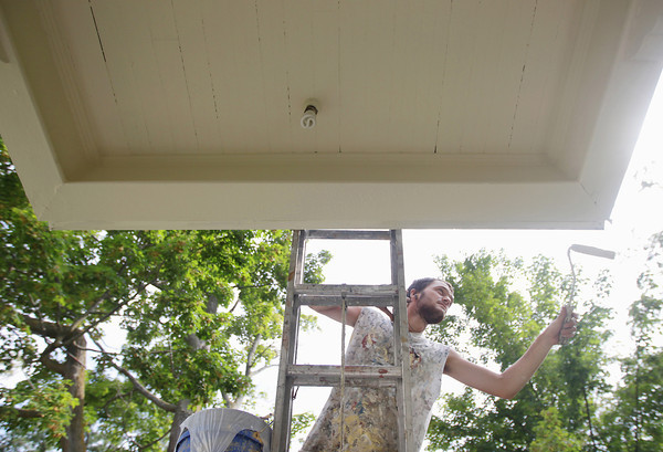 Record-Eagle/Keith King<br /> Colin Hoekje, with Student Painters, paints a porch overhang Wednesday, July 31, 2013 as part of a house-painting project in Traverse City.