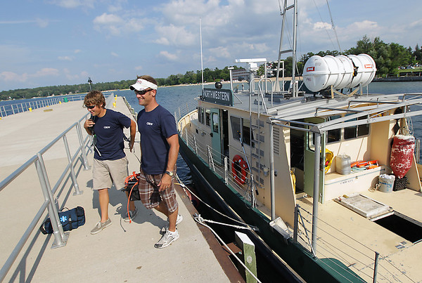 Record-Eagle/Keith King<br /> David Bearss, left, and Ryan Deering, who are with the field school run by the Nautical Archaeology Society through Northwestern Michigan College, leave the R/V Northwestern Thursday, August 4, 2011 at Northwestern Michigan College's Great Lakes Campus after finding what looks to be a barge in Grand Traverse Bay.