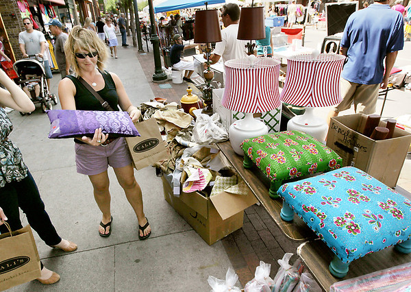 Record-Eagle/Keith King<br /> Andrea Burkholder, of Traverse City, looks at a pillow from Nest of Grand Traverse on Friday during the annual Downtown Street Sale.