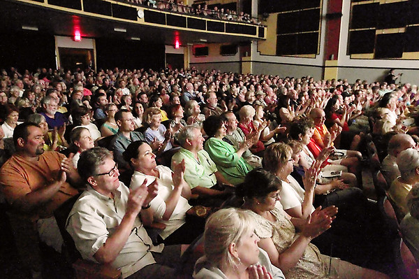 """Record-Eagle/Keith King<br /> Audience members applaud as Michael Moore reads stories from his book """"Here Comes Trouble"""" on Saturdayduring the Traverse City Film Festival's """"Mike's Surprise"""" event at Lars Hockstad Auditorium."""