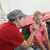 Record-Eagle/Keith King<br /> Lily VanWingerden, left, paints a cherry design on the cheek of Chloe Hall, 8, of Traverse City, during the 88th National Cherry Festival.
