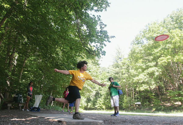 Record-Eagle/Keith King<br /> Kyle Peterson, of Muskegon, throws a disc as Nilla Dowdell, left, of Muskegon, and Isaac Piper, right, of Kingsley, look on during Teen Disc Golf at Hickory Hills Ski Area in Traverse City.