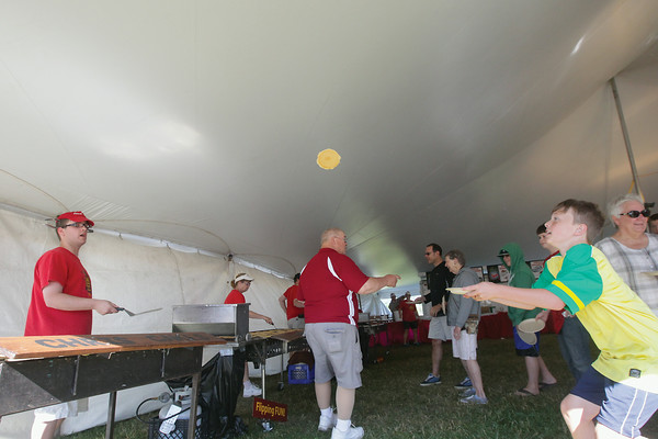 Record-Eagle/Keith King<br /> Jesse Prevallet, left, with Chris Cakes, flips a pancakes which is caught by Brice Kempf, 9, of Traverse City, during the Cherry Pancake Breakfast as part of the 88th National Cherry Festival.