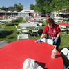 Record-Eagle/Keith King<br /> Lisa Kauffmann, volunteer, cleans a table covering as preparations are made on the opening day of the 88th National Cherry Festival.