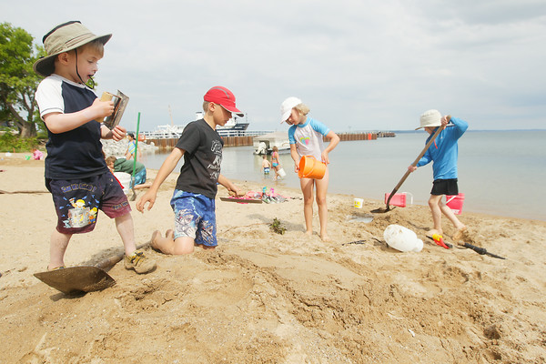 Record-Eagle/Keith King<br /> Augie Hamlin, from left, 6, of Houghton, Torrey Cookman, 10, of Marquette, Katie Cookman, 7, of Marquette and Cyrus Hamlin, 9, of Houghton, work on their sand sculpture for the Kids' Sand Sculpture Contest on the beach near the Traverse City Senior Center during the National Cherry Festival.