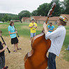 "Record-Eagle/Keith King<br /> Brennan Andes, of Ann Arbor, plays a double bass as he leads a group workshop Tuesday, July 9, 2013 during the SEEDS School of Rock camp at Twin Lakes Camp in Long Lake Township. A concert by camp students followed by musicians from Earthwork Music collective (who taught during the camp) is planned for Thursday beginning at 7:00 p.m. at the City Opera House. Funds raised from ticket sales for the event are for SEEDS School of Rock scholarship. For more information regarding tickets visit  <a href=""http://www.ecoseeds.org"">http://www.ecoseeds.org</a>."