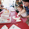 Record-Eagle/Keith King<br /> Grace Middlebrook, 4, of Cedar Springs, is held by her mother, Sara Middlebrook, as Grace paints an art project at the KidzArt and Artists Creating Together (ACT) station Wednesday during the National Cherry Festival Special Kids Day at the Open Space.