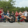 Record-Eagle/Keith King<br /> Participants pedal toward the finish line Saturday during the National Cherry Festival Kids' Big Wheel Race at the Grand Traverse County Civic Center.
