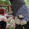 Record-Eagle/Keith King<br /> Jane Thompson, head of the Bay Area Yarn Bomb Society, attaches a knitted flamingo to a tree along the Jay P. Smith Walkway in Traverse City on Saturday during World Wide Knit and Crochet in Public Day.