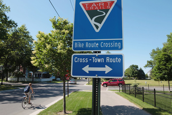 Record-Eagle/Keith King<br /> A bicyclist travels past a TART Trails bike route sign along Railroad Avenue near the intersection of Washington Street in Traverse City. Washington is an example of a road that functions well for cyclists as part of an in-town bike route, TART Trails Executive Director Julie Clark said. A new Traverse City committee will develop a non-motorized plan that considers walkers and bikers' needs.