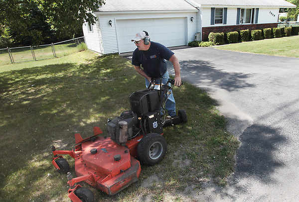 Record-Eagle/Keith King<br /> Norm McCoy, with the Grand Traverse County Commission on Aging, mows a lawn Tuesday in Traverse City.