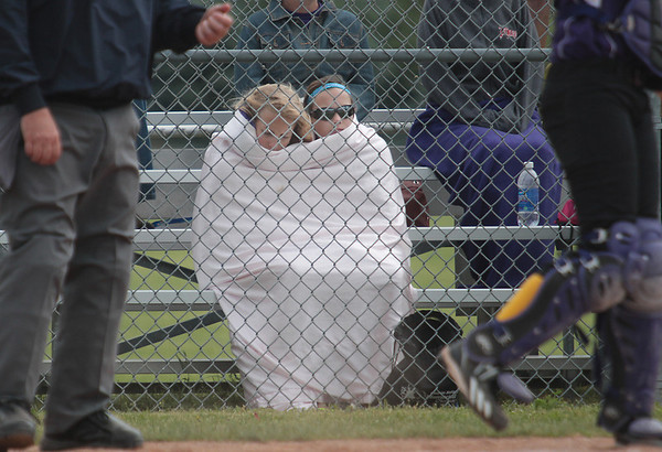 Record-Eagle/Keith King<br /> Erica Rubick, left, 13, of Gladstone, and Hayley Brockway, 14, of Rapid River, try to stay warm during the softball game between Bellaire and Rapid River on Tuesday at Traverse City West High School.