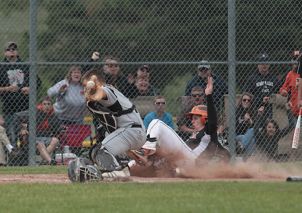 Record-Eagle/Keith King<br /> Mancelona's Damian Decker slides into home plate for the game-winning run as Newaygo's Larry Bulson III reaches to control the ball.
