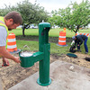 Record-Eagle/Keith King<br /> B.J. Roelofs, from left, with the City of Traverse City water and sewer maintenance department, flushes lines to remove air after a new drinking fountain and filtered water bottle filler is installed as Bill Rennie, working with the City of Traverse City water and sewer maintenance department, through Manpower, and Jim Schroeder, with the City of Traverse City water and sewer maintenance department, install a meter for the water station at the intersection of Grandview Parkway and Marina Drive, near the Open Space, in Traverse City.