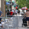 Record-Eagle/Keith King<br /> People use, and travel near, tables on the sidewalk along Union Street in downtown Traverse City.