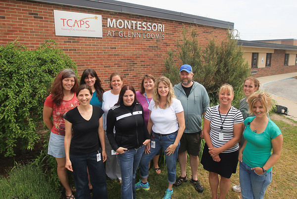 Record-Eagle/Keith King<br /> Angela Stricker, back row from left, teacher; Jen Girard, teacher; Amy McKean, assistant; Amy Belovich, teacher; Scott Munn, teacher; Cress Smith, teacher, as well as Angie Ballmer, front row from left, teacher, Lisa VanLoo, director; Liz Sievers, lead administrative assistant; Liz Vogel, teacher and Tracy Rucker, teacher, stand at the Traverse City Area Public Schools (TCAPS) Montessori at Glenn Loomis in Traverse City where a solar panel project is in the works.