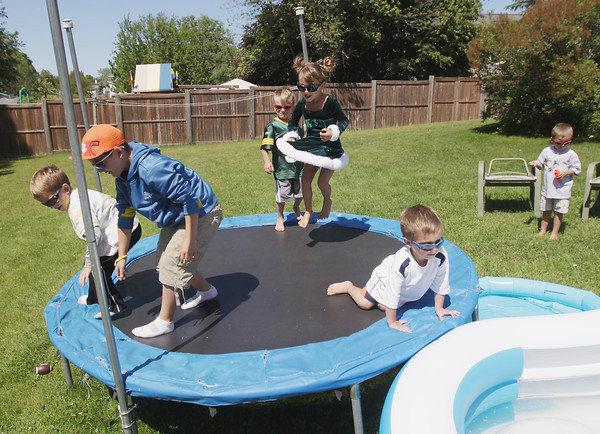 Record-Eagle/Keith King<br /> Caleb Lewandowski, from left, 7, Aiden Lewandowski, 9, Dane Lewandowski, 4, Summer Lewandowski, 4, Cameron Lewandowski, 4 and Brock Lewandowski, 4, of Traverse City, Friday, June 14, 2013 play in their backyard as their parents, Jeremy and Tonya Lewandowski (not pictured), stand near.