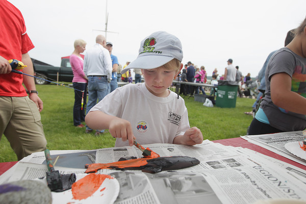 """Record-Eagle/Keith King<br /> Charlie May, 5, of Traverse City, paints an artificial fish as part of a Great Lakes Children's Museum art project called Gyotaku (from the Japanese words """"gyo"""" meaning fish, and """"taku"""" meaning rubbing, print or impression) Saturday, June 15, 2013 during the annual Kids' Free Fishing Day at the Northwestern Michigan College Great Lakes Campus."""