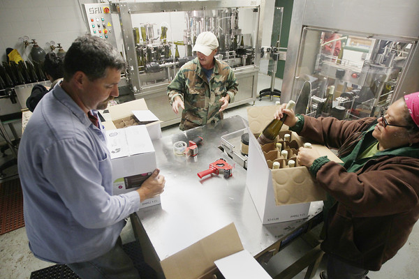 Record-Eagle/Keith King<br /> Richard Flores, from left, Rick Sparks and Diana Sparks work Thursday, June 13, 2013 as wine is bottled, labeled and packaged at Good Harbor Vineyards in Leland Township.