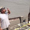 Record-Eagle/Keith King<br /> Nickolas Gonzalez, with Standfest Masonry, drinks a beverage with electrolytes near his co-worker, Jim Thiel, right, after finishing laying bricks for the day along the Masonic Hall building at the corner of Front and Union streets.
