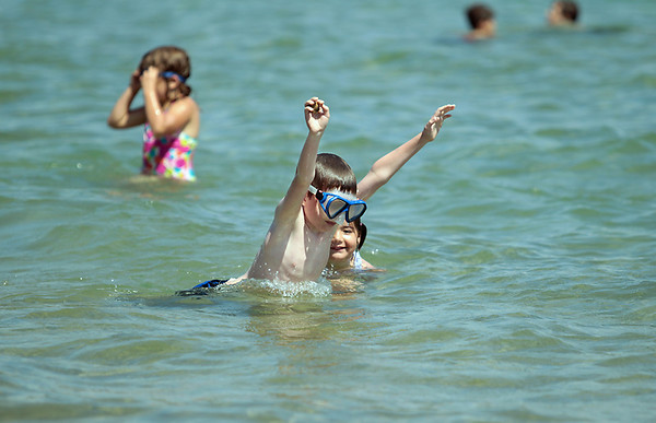 Record-Eagle/Keith King<br /> Grant Neuhardt, 8, of Traverse City, dives while Ella Neuhardt, 6, swims behind him near Haserot Beach on Old Mission Peninsula. Temperatures reached 91 degrees in Traverse City on Wednesday according to the National Weather Service, but a cold front moving in was expected to drop temperatures back to seasonal levels in the 70s for the next several days. The hot weather ramped up electricity use from local utilities, as Traverse City Light and Power reported a peak load of 67.5 mega watts at mid-afternoon, the highest so far in 2012.