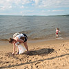 Record-Eagle/Keith King<br /> Kate Daggett, of Traverse City, picks up trash along a beach on West Grand Traverse Bay as her daughter, Charlotte Daggett, 4, plays nearby.