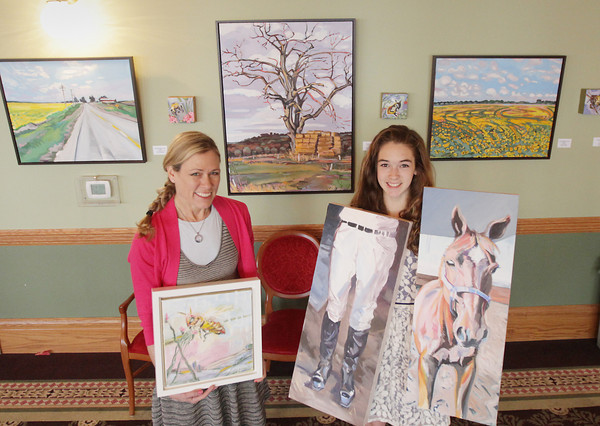 Record-Eagle/Keith King<br /> Lindy Bishop, left, of Traverse City, and Olivia Bishop, 14, stand Tuesday, April 30, 2013 with and near their artwork displayed at the City Opera House.