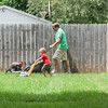"""Record-Eagle/Keith King<br /> Patrick Gerber, of Traverse City, mows his lawn Friday as his son, Maddox Gerber, 2, walks next to him with a toy mower. """"He loves doing it,"""" Patrick said."""