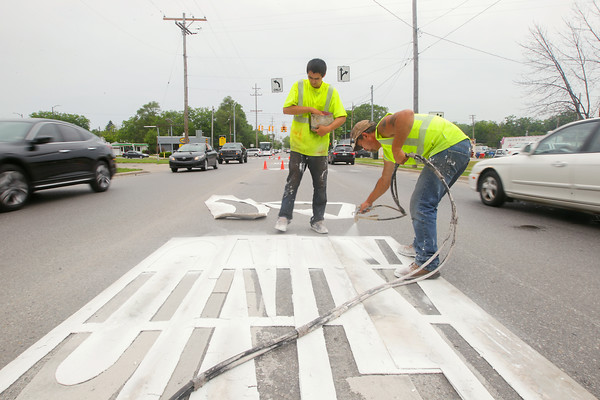 Record-Eagle/Keith King<br /> Austin Jameson, left, with M & M Pavement Marking, applies glass beads for reflectivity as Troy Brown, with M & M Pavement Marking, applies paint for markings on South Garfield Avenue near East Eighth Street in Traverse City.